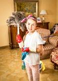 Muchacha sonriente que hace la limpieza que presenta con el cepillo de la pluma Imagen de archivo libre de regalías