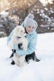 Muchacha sonriente que juega con su perro Imagen de archivo