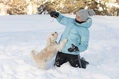 Muchacha sonriente que juega con su perro Imagenes de archivo