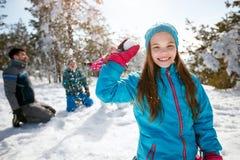 Muchacha sonriente que juega en nieve en el día de fiesta del esquí en montañas imágenes de archivo libres de regalías