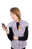 Muchacha sonriente que lee el mensaje divertido en su teléfono móvil aislado en blanco Fotos de archivo