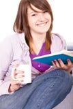 Muchacha sonriente que lee un libro Imagen de archivo