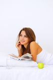 Muchacha sonriente que lee un libro Foto de archivo libre de regalías