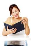 Muchacha sonriente que lee un libro. Imagenes de archivo