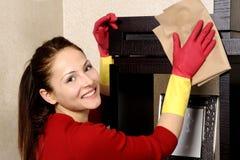 Muchacha sonriente que limpia la casa Imágenes de archivo libres de regalías