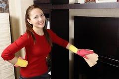 Muchacha sonriente que limpia la casa Imagen de archivo