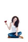 Muchacha sonriente que lleva a cabo el símbolo del corazón que se sienta en el piso Foto de archivo libre de regalías