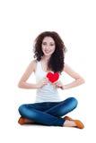 Muchacha sonriente que lleva a cabo el símbolo del corazón que se sienta en el piso Imagen de archivo libre de regalías