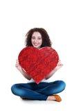 Muchacha sonriente que lleva a cabo el símbolo del corazón que se sienta en el piso Fotos de archivo libres de regalías