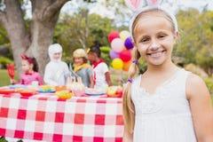 Muchacha sonriente que lleva un traje durante una fiesta de cumpleaños Imagenes de archivo