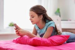 Muchacha sonriente que manda un SMS en smartphone en casa Fotografía de archivo