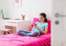 Muchacha sonriente que manda un SMS en smartphone en casa Foto de archivo
