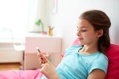 Muchacha sonriente que manda un SMS en smartphone en casa Fotos de archivo
