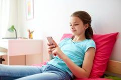 Muchacha sonriente que manda un SMS en smartphone en casa Foto de archivo libre de regalías