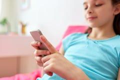 Muchacha sonriente que manda un SMS en smartphone en casa Fotos de archivo libres de regalías