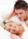 Muchacha sonriente que miente con su novio Foto de archivo