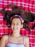 Muchacha sonriente que miente en ella detrás en una manta Fotografía de archivo libre de regalías