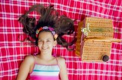Muchacha sonriente que miente en ella detrás en una manta y que se relaja Fotografía de archivo