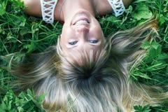 Muchacha sonriente que miente en la hierba Foto de archivo