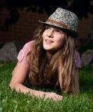 Muchacha sonriente que miente en la hierba en el jardín en n Fotos de archivo libres de regalías