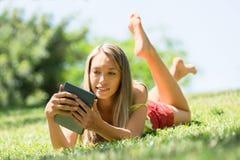 Muchacha sonriente que miente en la hierba que goza leyendo el ereader Imágenes de archivo libres de regalías