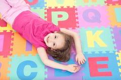 Muchacha sonriente que miente en los azulejos del alfabeto Fotos de archivo libres de regalías