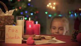 Muchacha sonriente que mira hacia fuera bajo la tabla y tomar la galleta tradicional de Navidad del jengibre almacen de metraje de vídeo
