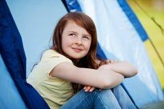 Muchacha sonriente que mira para arriba mientras que se sienta en tienda Imagenes de archivo