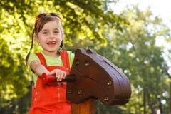Muchacha sonriente que monta el caballo de madera en el patio Fotografía de archivo libre de regalías