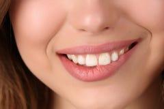 Muchacha sonriente que muerde su labio Cierre para arriba Fotografía de archivo