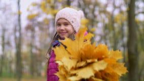 Muchacha sonriente que muestra el bouguet de las hojas de otoño almacen de video