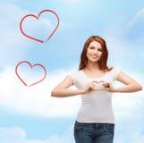 Muchacha sonriente que muestra el corazón con las manos Foto de archivo libre de regalías