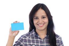 Muchacha sonriente que muestra la tarjeta en blanco Imagen de archivo