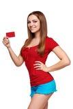 Muchacha sonriente que muestra la tarjeta roja a disposición Foto de archivo libre de regalías