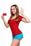 Muchacha sonriente que muestra la tarjeta roja a disposición Fotografía de archivo