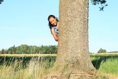 Muchacha sonriente que oculta detrás de árbol Foto de archivo libre de regalías