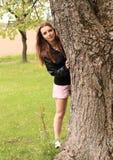Muchacha sonriente que oculta detrás de árbol Fotos de archivo libres de regalías