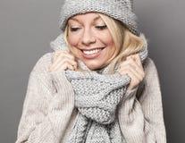 Muchacha sonriente que permanece caliente en para arriba envuelta bufanda acogedora del invierno imagenes de archivo