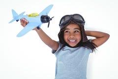 Muchacha sonriente que pone en el piso que juega con el aeroplano del juguete Imagen de archivo libre de regalías