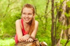 Muchacha sonriente que pone en el registro en el día soleado Imágenes de archivo libres de regalías