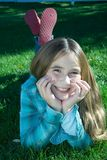 Muchacha sonriente que pone en hierba Fotos de archivo libres de regalías