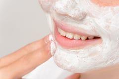 Muchacha sonriente que pone la limpieza facial de los fingeres de la máscara Imagenes de archivo
