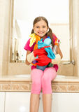Muchacha sonriente que presenta con las despedregadoras en botellas en el cuarto de baño Imagen de archivo libre de regalías