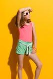 Muchacha sonriente que presenta en las gafas de sol y que mira lejos Foto de archivo libre de regalías
