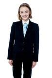 Muchacha sonriente que presenta en traje de negocios Imagenes de archivo
