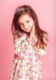 Muchacha sonriente que presenta sobre rosa en sitio Imagen de archivo