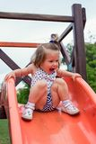 Muchacha sonriente que resbala abajo en diapositiva Imágenes de archivo libres de regalías