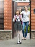 Muchacha sonriente que sale la casa a la escuela Madre que se coloca en d Fotografía de archivo