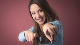Muchacha sonriente que señala en la cámara Fotos de archivo libres de regalías