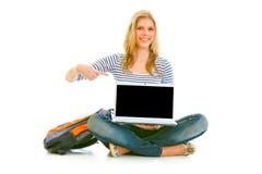 Muchacha sonriente que señala en la computadora portátil con la pantalla en blanco Imagenes de archivo